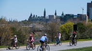 People ride their bikes on the westbound lane of the Sir John A. Macdonald Parkway in Ottawa, as it is closed to motor vehicle traffic to allow people to get fresh air while practising physical distancing during the COVID-19 pandemic, on the Victoria Day long weekend, Monday, May 18, 2020. THE CANADIAN PRESS/Justin Tang