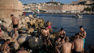 Sunbathers enjoy the sunset at the entrance to Marseille's Old Port in southern France, Tuesday, May 26, 2020 as France gradually lifts its COVID-19 lockdown. (AP Photo/Daniel Cole)