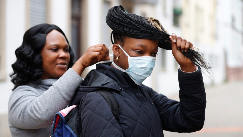 A mother attaches his daughter' s mask outside a school in Strasbourg, eastern France, Thursday, May 14, 2020. The government has allowed parents to keep children at home amid fears prompted by the COVID-19, as France is one of the hardest-hit countries in the world. Authorities say 86% of preschools and primary schools are reopening this week. (AP Photo/Jean-Francois Badias)