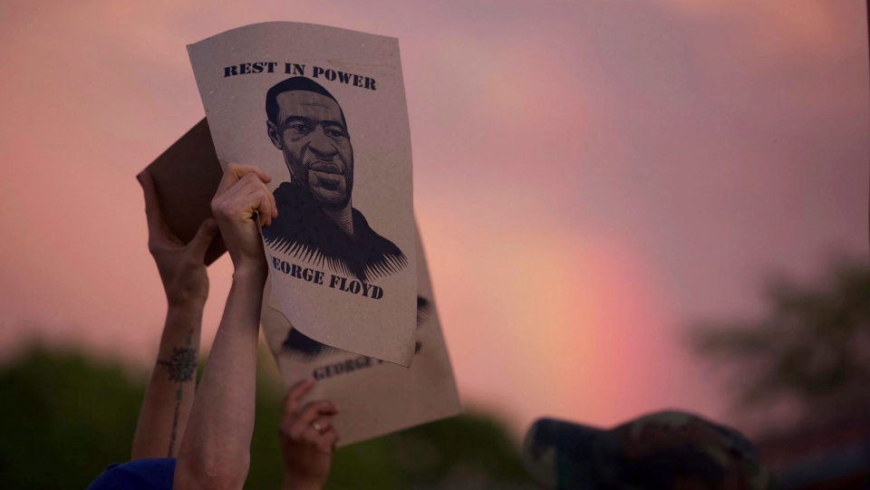 A protester holds a sign with an image of George Floyd during protests Wednesday, May 27, 2020, in Minneapolis against the death of Floyd in Minneapolis police custody earlier in the week. (Christine T. Nguyen/Minnesota Public Radio via AP)