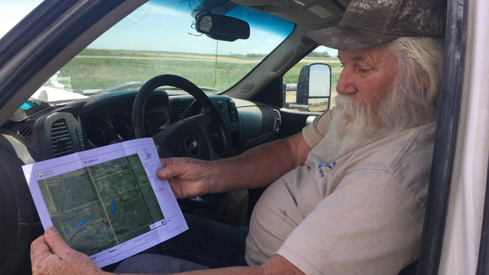 Doug Brownridge looks over a map he received from the province regarding the flow of effluent water from the Town of Arcola lagoon. (Cole Davenport/CTV News)