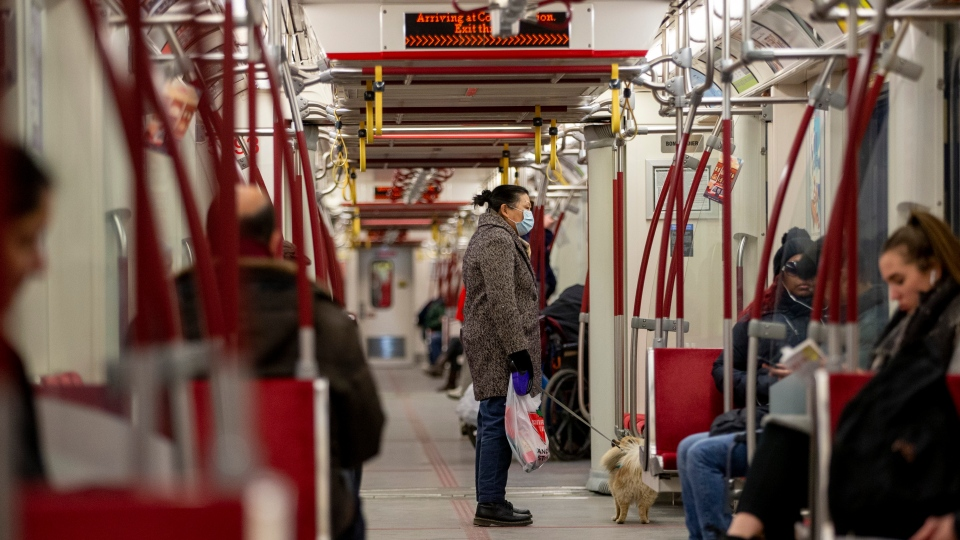 A woman wears a mask while riding the Bloor line subway amid coronavirus fears spreading in Toronto on Saturday, March 14, 2020. THE CANADIAN PRESS/Carlos Osorio