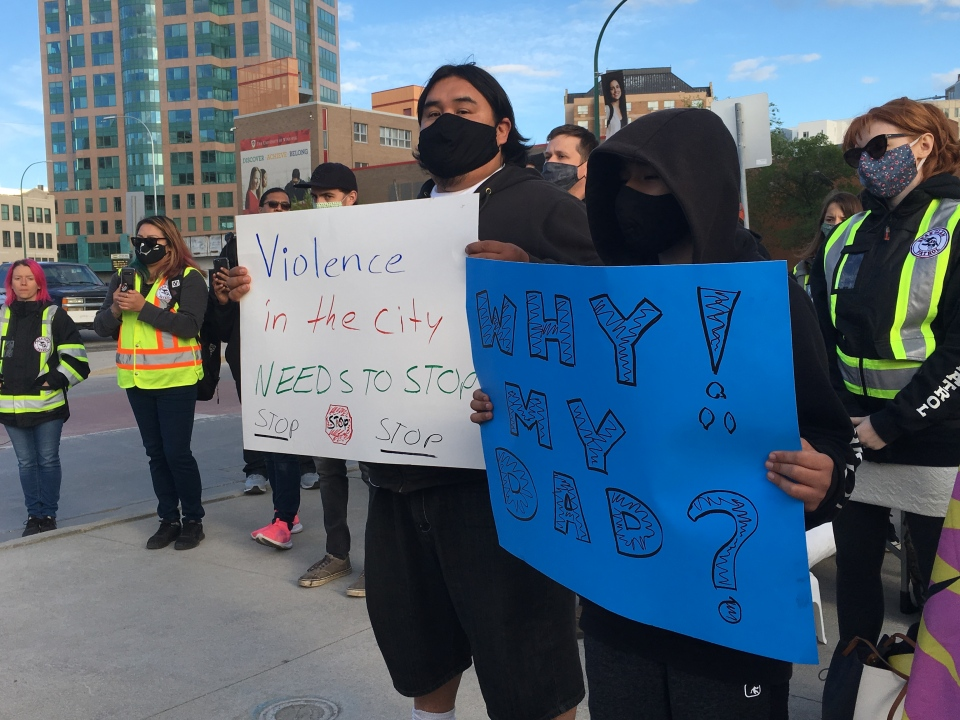 Dozens attended a vigil held for 57-year-old Raymond Wesley Hill Friday night at the same corner where he was fatally stabbed on a Winnipeg Transit Bus. Some held signs in a demonstration against violence in the city.