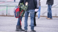 A boy hugs his father as he waits to be called to enter the schoolyard the Marie-Derome School in Saint-Jean-sur-Richelieu, Que. on Monday, May 11, 2020. Quebec's education department says a total of 41 students and teachers have tested positive for COVID-19 since primary schools outside the Montreal area opened on May 11. THE CANADIAN PRESS/Paul Chiasson