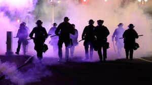 Policemen walk enveloped by teargas in Portland, Friday, March 29, 2020. (Dave Killen/The Oregonian via AP)