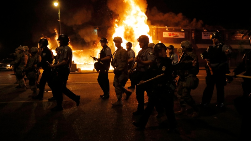 Police clear the street for firefighters during protests Friday, May 29, 2020, in Minneapolis.  (AP Photo/Julio Cortez)