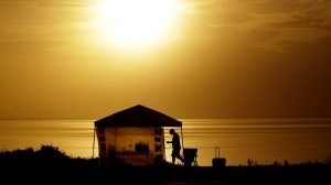 A man sets up his camp along the Indian River Lagoon at sunrise Saturday, May 30, 2020, at Titusville, Fla. as he waits to watch the launch of the SpaceX Falcon 9, with Dragon crew capsule on top of the rocket. (AP Photo/Charlie Riedel)