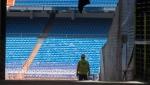 Workers walk into Real Madrid's Santiago Bernabeu stadium in Madrid, Spain, Monday, May 25, 2020. (AP Photo/Paul White)