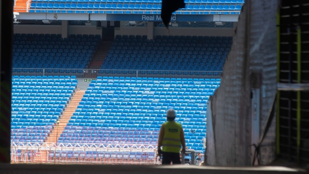 Workers walk into Real Madrid's Santiago Bernabeu stadium in Madrid, Spain, Monday, May 25, 2020. (AP Photo/Paul White)