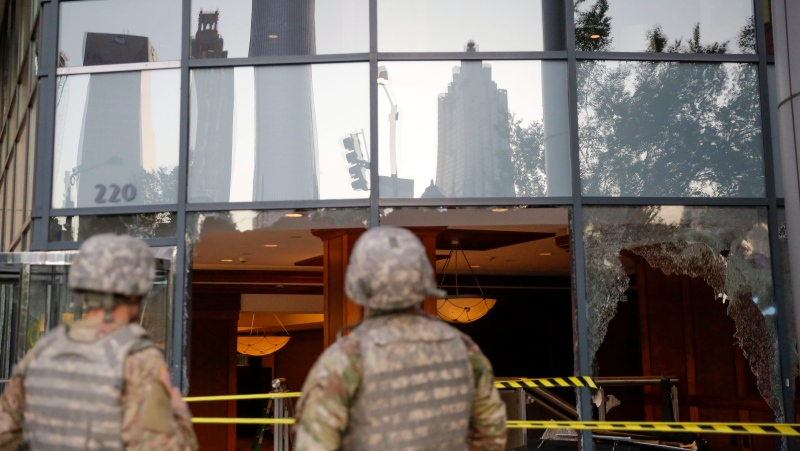 The National Guard looks at the damage done to downtown Atlanta in the aftermath of a demonstration against police violence on Saturday, May 30, 2020, in Atlanta. (AP Photo/Brynn Anderson)