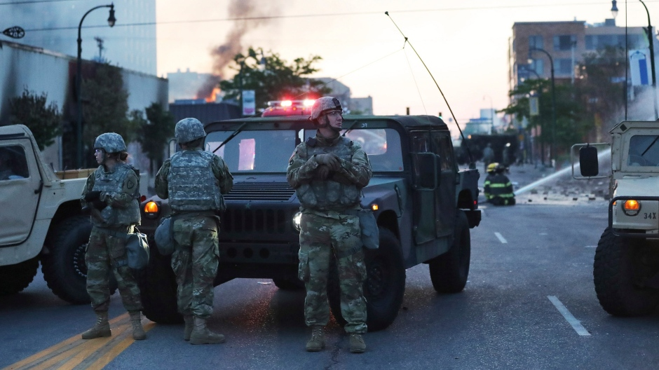 Minnesota National Guard members maintain a position on Lake St., near S. Chicago Ave., protecting nearby firefighters following protests in the death of George Floyd, Saturday, May 30, 2020, in Minneapolis, Minn. (David Joles/Star Tribune via AP)