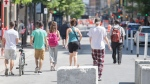People walk along an extended sidewalk on Sainte-Catherine street in Montreal, Saturday, May 30, 2020, as the COVID-19 pandemic continues in Canada and around the world. THE CANADIAN PRESS/Graham Hughes