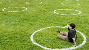 A man sips his beer while sitting in environmentally friendly physical distancing circles at Trinity Bellwoods Park during the COVID-19 pandemic in Toronto on Thursday, May 28, 2020.  (Nathan Denette/The Canadian Press)
