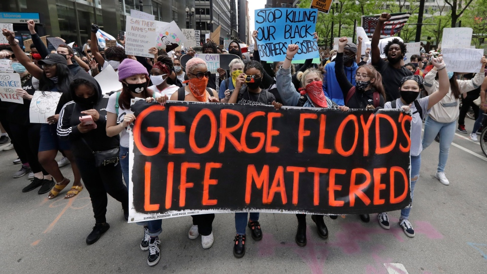 Protesters hold signs as they march during a protest over the death of George Floyd in Chicago, Saturday, May 30, 2020. Floyd died after being taken into custody and restrained by Minneapolis police on Memorial Day in Minnesota. (AP Photo/Nam Y. Huh)