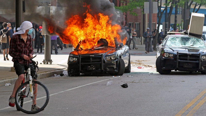 Protesters watch as a Cleveland police cruiser burns near the Justice Center during a rally seeking justice in the death of George Floyd, Saturday, May 30, 2020 in Cleveland. Protests were held throughout the country over the death of Floyd, a black man who died after being restrained by Minneapolis police officers on May 25. (John Kuntz/The Plain Dealer via AP)