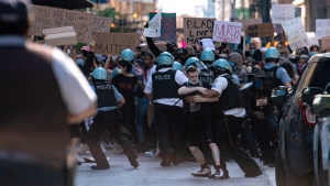 Chicago police confront protesters near Daley Plaza, in Chicago, Ill., Saturday, May 30, 2020, during a protest over the death of George Floyd, who died in police custody on Memorial Day in Minneapolis. (Tyler LaRiviere/Chicago Sun-Times via AP)
