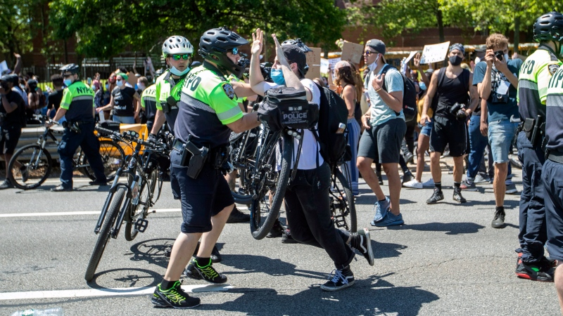 A police officer uses his bicycle to shove a demonstrator during a solidarity rally for George Floyd, Saturday, May 30, 2020, in New York. Floyd died after Minneapolis police officer Derek Chauvin pressed his knee into his neck for several minutes even after he stopped moving and pleading for air. (AP Photo/Mary Altaffer)