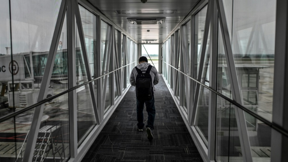 A passenger walks along an airbridge at Tianhe Airport in Wuhan. (AFP)