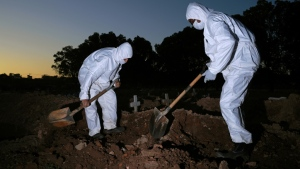 Workers wear protective clothing to bury a COVID-19 victim at the Sao Franciso Xavier cemetery in Rio de Janeiro, Brazil on May 29, 2020. (AFP)