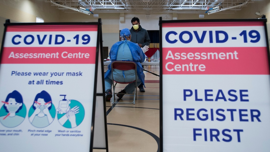 Muhammad Junayed, centre back, gets instructions for being tested for COVID-19 from a health care worker at a pop-up testing centre at the Islamic Institute of Toronto during the COVID-19 pandemic in Scarborough, Ont., on Friday, May 29, 2020. (Nathan Denette/The Canadian Press)