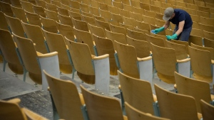 A worker is seen cleaning the seats of the auditorium at Eric Hamber Secondary school in Vancouver, B.C., Monday, March 23, 2020. Schools in British Columbia are set to reopen Monday. THE CANADIAN PRESS/Jonathan Hayward