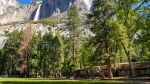 """In this May 27, 2020, photo provided by the National Park Service, Yosemite Valley School, lower right, stands in Yosemite National Park, Calif. In the background is Upper Yosemite Falls. The school, the only one inside the 1,200-sq. mile (3,100-sq. kilometer) Yosemite park, shut its doors in mid-March due to the coronavirus pandemic like others across America and class has been convening online. But the pandemic hasn't stopped the presses on the school year's last edition of """"The Yosemite Eye,"""" a publication that has so charmed its community it boasts a circulation of nearly 5,000 copies. (Jamie Richards/National Park Service via AP)"""