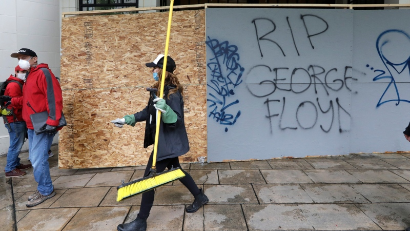 A woman helping to clean up downtown walks past graffiti Sunday, May 31, 2020, in Seattle, following a night of unrest and protests over the death of George Floyd, a black man who was in police custody in Minneapolis. Floyd died after being restrained by Minneapolis police officers on May 25. (AP Photo/Elaine Thompson)