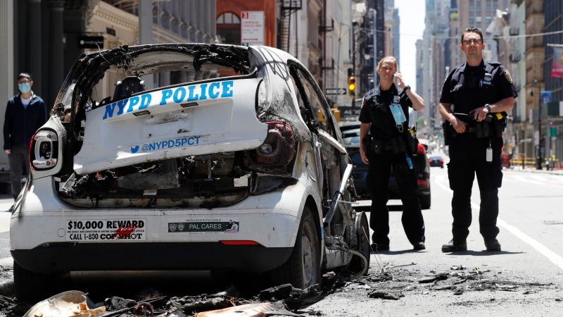 Officers stand guard beside a burned-out mini-New York Police Department vehicle, abandoned on Broadway in Lower Manhattan, Sunday, May 31, 2020, in New York, following a night of violence and protests in New York. People took to the streets to protest the death of George Floyd, who was in police custody when he died on Memorial Day in Minneapolis. (AP Photo/Kathy Willens)