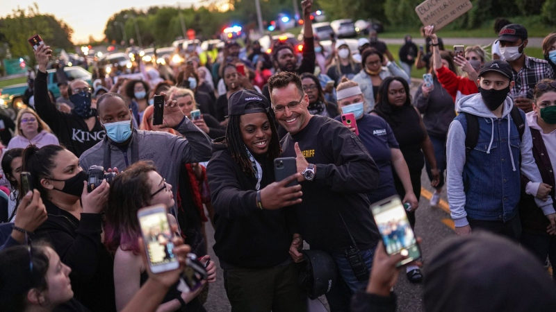 Johnie Franklin of Flint takes a selfie with Genesee County Sheriff Chris Swanson as he marches with protesters against police brutality and in memory of George Floyd on Saturday in Flint Township, Michigan. (Ryan Garza/USA TODAY NETWORK/Reuters)