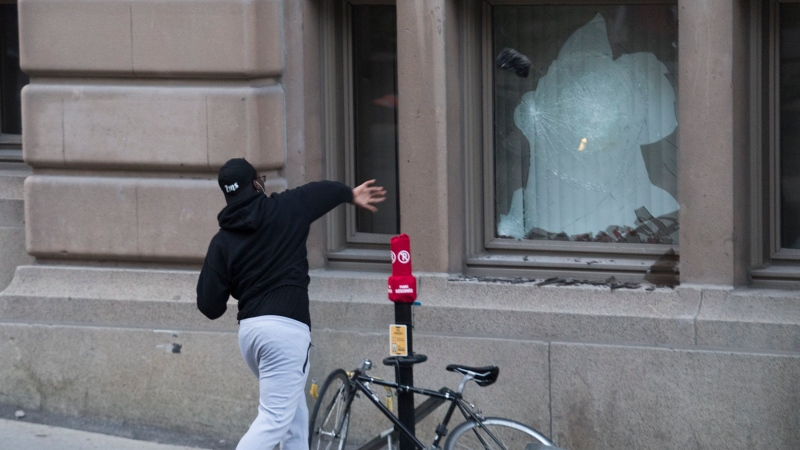 A man throws a rock through a window during a demonstration calling for justice in the death of George Floyd and victims of police brutality in Montreal, Sunday, May 31, 2020.THE CANADIAN PRESS/Graham Hughes
