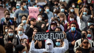A man holds a skateboard bearing George Floyd's name above his head as thousands of people gather for a peaceful demonstration in support of Floyd and Regis Korchinski-Paquet and protest against racism, injustice and police brutality, in Vancouver, on Sunday, May 31, 2020. THE CANADIAN PRESS/Darryl Dyck