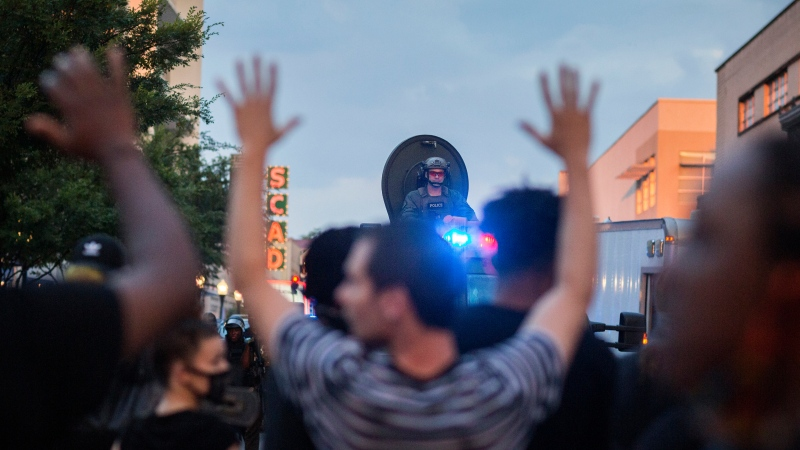 "Protesters hold hands up and chant ""don't shoot"" during a standoff with Savannah police after a peaceful rally, Sunday, May 31, 2020, over the death of George Floyd in Minneapolis. (Stephen B. Morton/Atlanta Journal-Constitution via AP)"