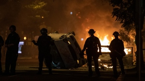 Police stand near an overturned vehicle and a fire as demonstrators protest the death of George Floyd, Sunday, May 31, 2020, near the White House in Washington. Floyd died after being restrained by Minneapolis police officers (AP Photo/Alex Brandon)