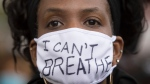 A woman attends a demonstration calling for justice for George Floyd in Montreal, Sunday, May 31, 2020. (THE CANADIAN PRESS/Graham Hughes)