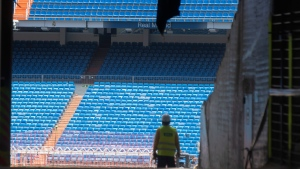 Workers walk into Real Madrid's Santiago Bernabeu stadium in Madrid, Spain, Monday, May 25, 2020. Spanish league clubs are now allowed to train with groups of up to 14 players as the league stays on track to restart in less than three weeks. (AP Photo/Paul White)