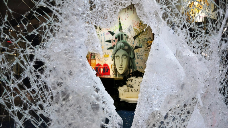A Statue of Liberty painting is seen through a smashed Dolce and Gabbana store window in the SoHo neighbourhood of New York, on June 1, 2020. (Mark Lennihan / AP)