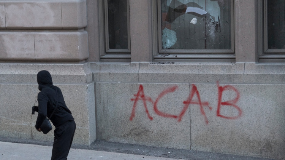 A protester throws a rock through a window during a demonstration calling for justice in the death of George Floyd and victims of police brutality in Montreal, Sunday, May 31, 2020.THE CANADIAN PRESS/Graham Hughes