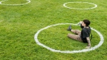 A man sips his beer while sitting in physical distancing circles at Trinity Bellwoods Park during the COVID-19 pandemic in Toronto on Thursday, May 28, 2020. (THE CANADIAN PRESS/Nathan Denette)