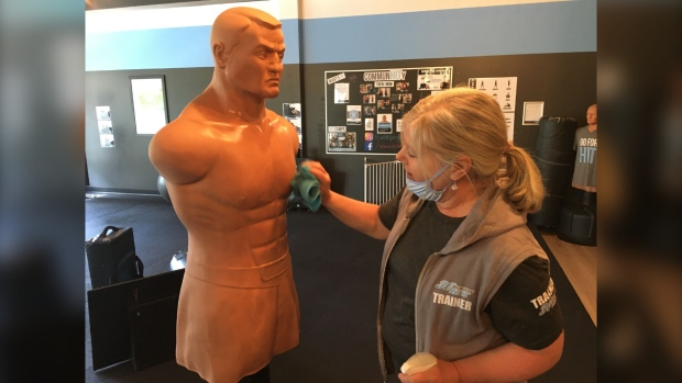 Allison Bell cleans equipment at 30 Minute Hit on Corydon Ave. The kickboxing style gym reopened Monday for the first time since March 16. (CTV News Photo Michelle Gerwing)