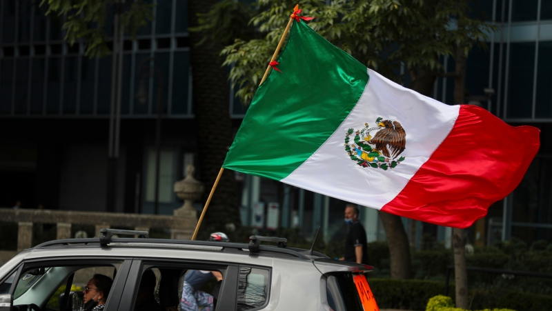 A woman, with a national flag attached to her car, takes part in a nationwide car caravan protest demanding the resignation of President Andres Manuel Lopez Obrador, commonly referred to by his initials AMLO, organized by the Frente Nacional anti AMLO or National Front Against AMLO, in Mexico City, Saturday, May 30, 2020. The group decided on a car caravan protest in order to maintain social distancing as a precaution against the spread of the new coronavirus. (AP Photo/Fernando Llano)