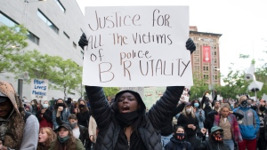 A protester holds up a sign during a demonstration calling for justice in the death of George Floyd and victims of police brutality in Montreal, Sunday, May 31, 2020.THE CANADIAN PRESS/Graham Hughes