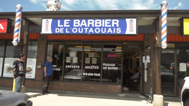 Customers wait outside Le barbier de l'Outaouais in Gatineau for their turn to get a haircut on the first day barbers and salons are allowed to open in Quebec since the COVID-19 pandemic began. (Leah Larocque / CTV News Ottawa)