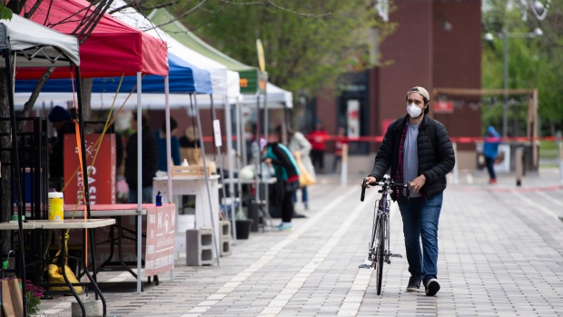 A customer is alone as they walk their bike to pick up an order at the Ottawa Farmers' Market at Lansdowne Park, which opened for online order pickups only due to the COVID-19 pandemic, in Ottawa, on Sunday, May 31, 2020. (Justin Tang/THE CANADIAN PRESS)