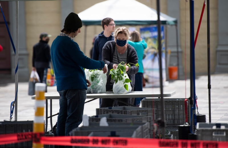 A customer picks up an order at the Ottawa Farmers' Market at Lansdowne Park, which opened for online order pickups only due to the COVID-19 pandemic, in Ottawa, on Sunday, May 31, 2020.  (Justin Tang/THE CANADIAN PRESS)