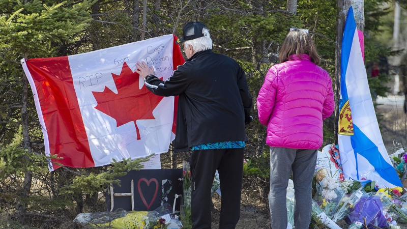 A couple place a flag at a memorial in Portapique, N.S. on Wednesday, April 22, 2021. RCMP say at least 22 people are dead after a man who at one point wore a police uniform and drove a mock-up cruiser, went on a murder rampage in Portapique and several other Nova Scotia communities. THE CANADIAN PRESS/Andrew Vaughan