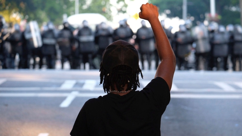 A demonstrator holds up a fist near a line of police during a protest Monday, June 1, 2020, in Atlanta over the death of George Floyd, who died May 25 in Minneapolis. (Ben Gray/Atlanta Journal-Constitution via AP)
