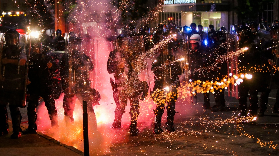 Fireworks go off in front of police, who with protesters in front of police headquarters in St. Louis on Monday, June 1, 2020. (Colter Peterson/St. Louis Post-Dispatch via AP)