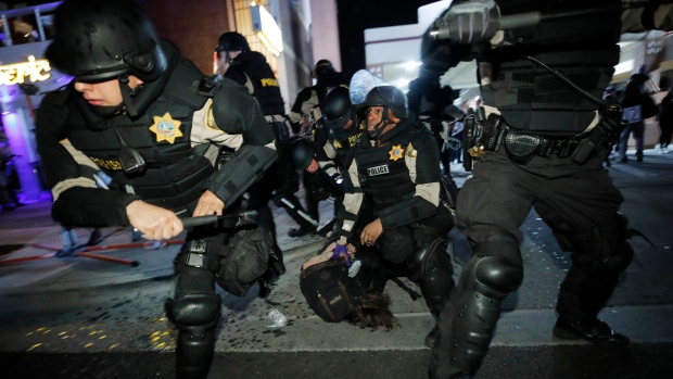 Police knock back protesters as they detain one at a rally Saturday, May 30, 2020, in Las Vegas, over the death of George Floyd, a black man who was in police custody in Minneapolis. (AP Photo/John Locher)