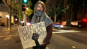 A protester from St. Louis, U.S., who gave her name as Merinda, carries a handmade sign as demonstrators gather in Sydney, Tuesday, June 2, 2020, to support the cause of U.S. protests over the death of George Floyd and urged their own governments to address racism and police violence. (AP Photo/Rick Rycroft)