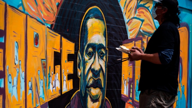 A group of artists paint a mural of George Floyd on the wall outside of Cup Foods, where Floyd was killed in police custody, on May 28, 2020 in Minneapolis, Minnesota. (Stephen Maturen/Getty Images North America/Getty Images)